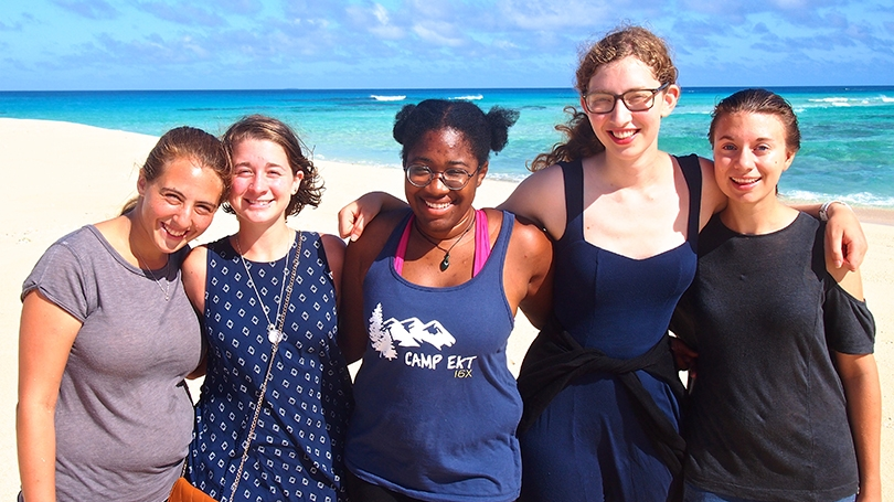 a group of female students standing together on a beach