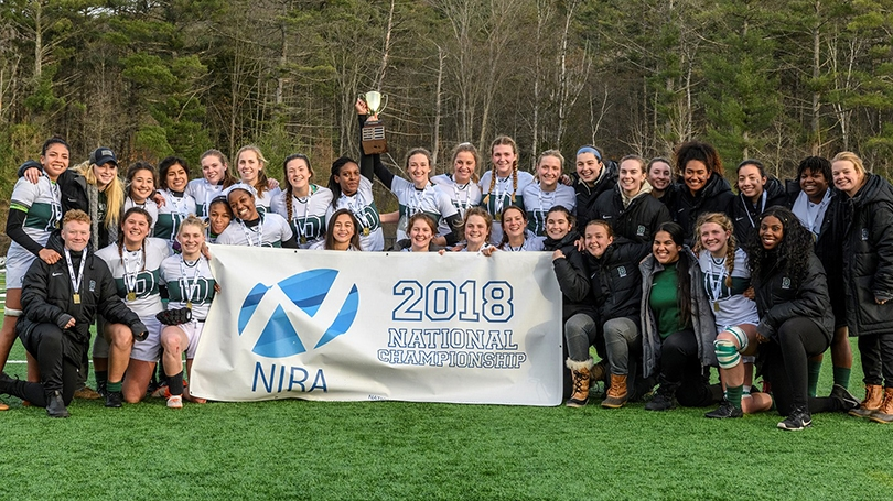 the women's rugby team posing with a white and blue banner that reads 2018 National Championship