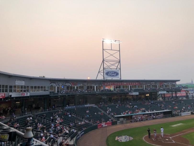 The sun sets behind a baseball stadium