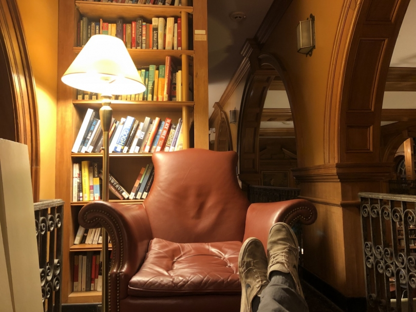a leather chair with bookshelf behind
