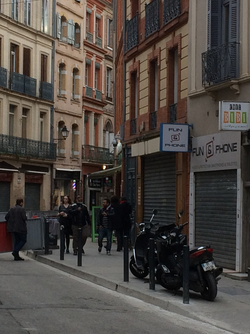 street in Toulouse with brick buildings with pastel trim