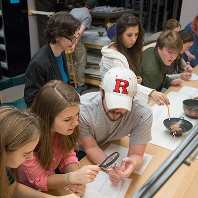 A photo of students examining artifacts in an Introduction to Classical Archaeology class