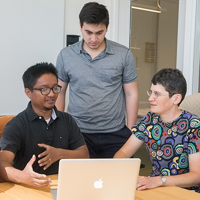 A photo of students and a professor discussing a project