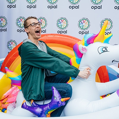 A photo of a student on an inflatable unicorn during a PRIDE event