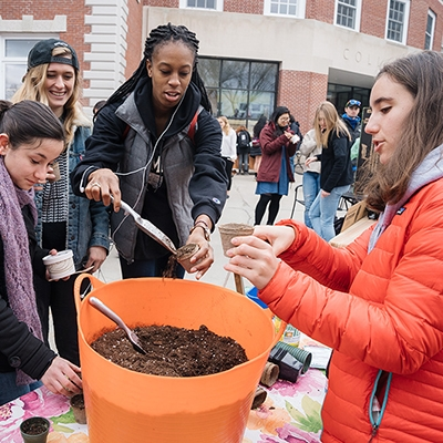 A photo of students looking at soil