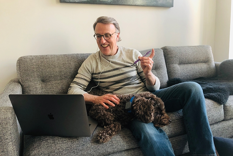 A photo of Dean Coffin and his dog recording a podcast