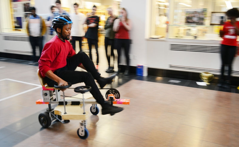 A photo of a student riding an omnidirectional vehicle