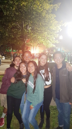 a group of students posing for a photo in front of the homecoming bonfire