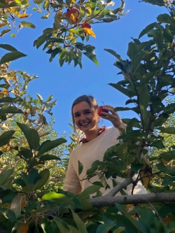 Abbi standing on a ladder and holding an apple, surrounded by the leaves of an apple tree.