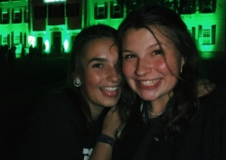 Abbi and a friend taking a selfie in front of Dartmouth Hall, which is lit in green for homecoming.