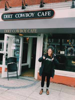 Abbi giving 2 thumbs up in front of Dirt Cowboy Cafe, a small coffee shop with lots of windows