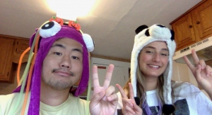 Two people wearing animal hats sitting next to each other.