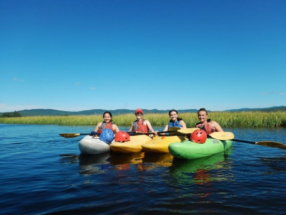 Abbi kayaking with 3 other friends on a large lake with mountains in the background
