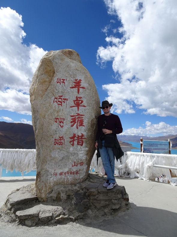 Gui posing in front of a large stone monument