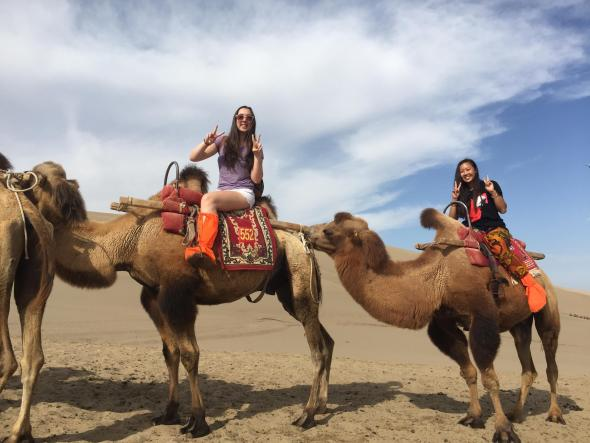 Colleen riding a camel through the Gobi Desert