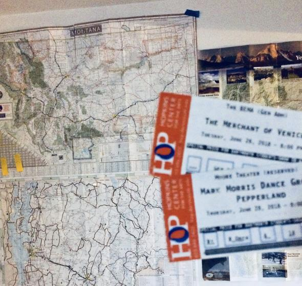 Merchant of Venice and Pepperland tickets in front of wall maps