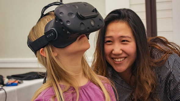 a woman watching a young girl trying out a virtual reality device
